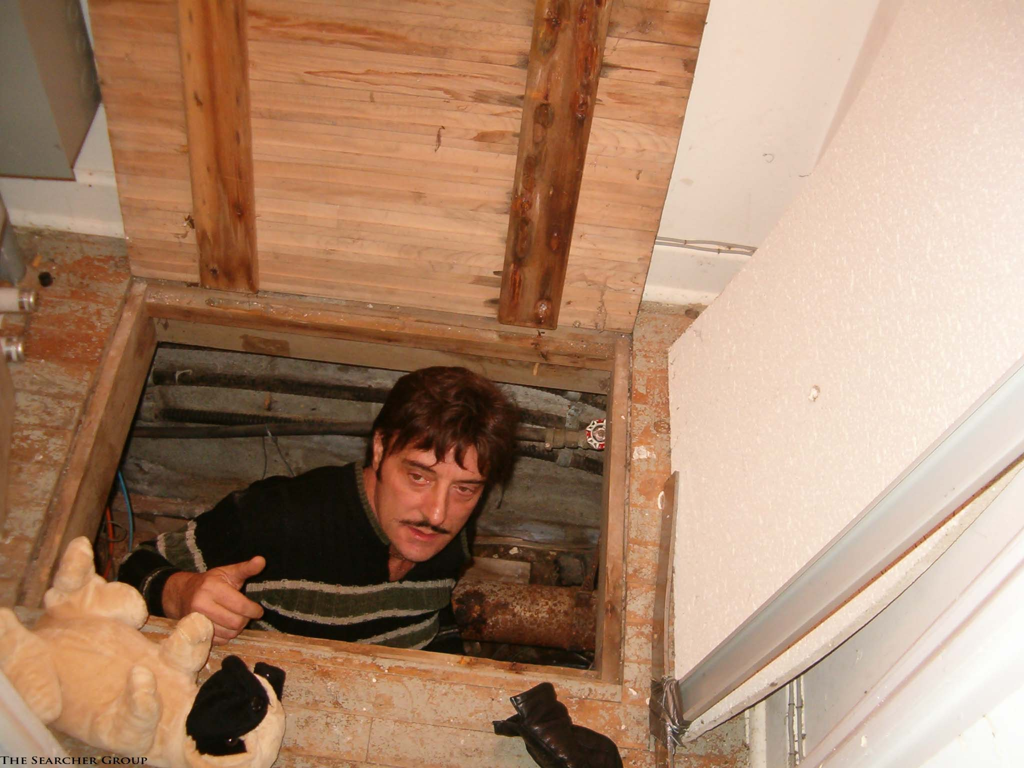 Paul searching in crawl space in house