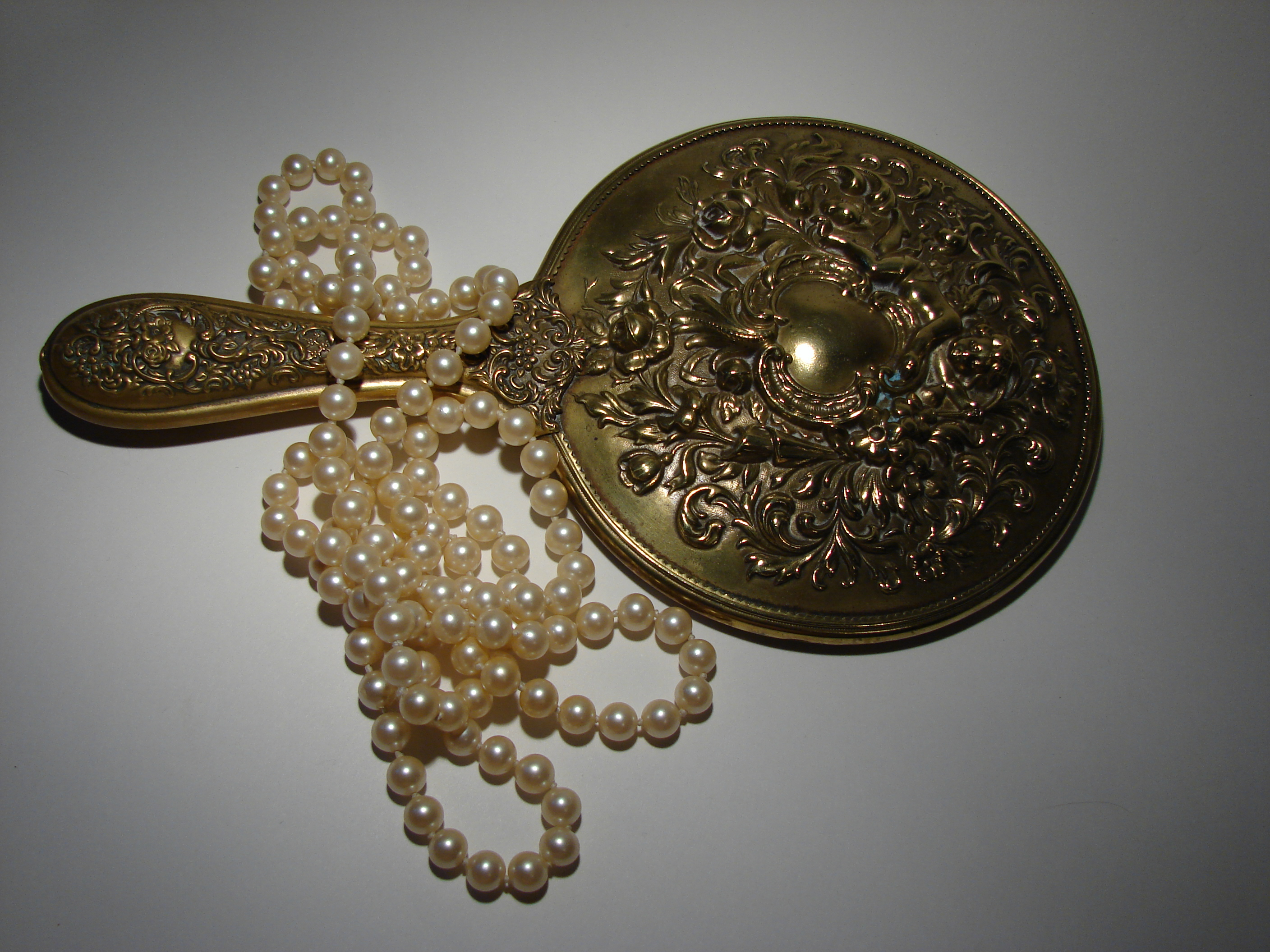 Photo of antique hand held mirror and pearl necklace
