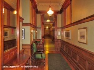 Interior Photo of Queen's Park showing hallway with green chair and carpet