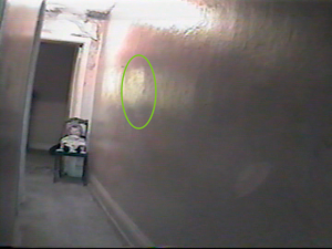 Screen capture of a hallway with a doll on a chair at end of hall facing camera and lights along wall there is a circle drawn around the image of a persons face in the lights on the wall