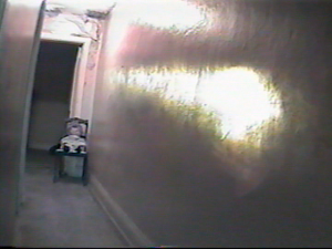 Screen capture of a hallway with a doll on a chair at end of hall facing camera and lights along wall