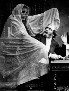 black and white picture of a spirit cloaked in white material standing over a man who is seated at a table